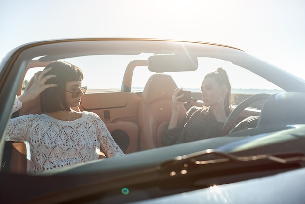 Twee gelukkige vrouwen in de cabriolet die elkaar fotograferen