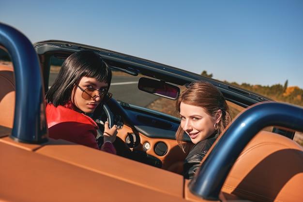 Twee gelukkige vrouwen in de cabriolet rijden en hebben plezier achteraanzicht