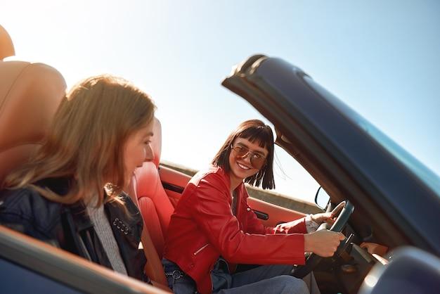 Twee gelukkige vrouwen in de cabriolet rijden en hebben plezier