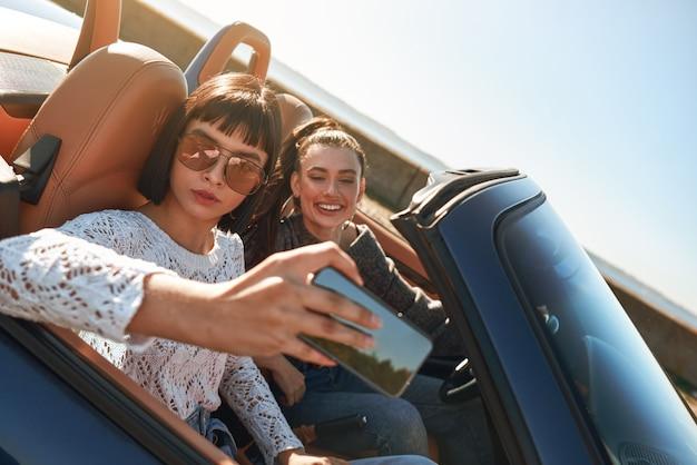 Twee gelukkige vrouwen in de cabriolet rijden met plezier en nemen selfie