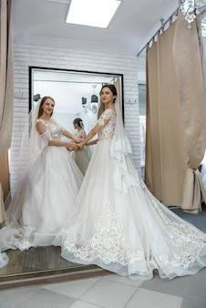Twee gelukkige vrouwen in trouwjurken poseren in salon