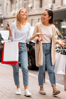 Twee gelukkige vrouwen lopen op straat met boodschappentassen