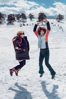 Twee gelukkige vrouwen springen in de lucht en hebben plezier in sneeuw op de zonnige winterdag.