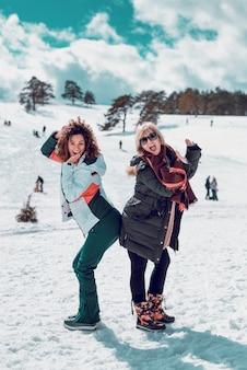 Twee gelukkige vrouwen staan en hebben plezier in de sneeuw