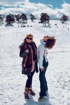 Twee gelukkige vrouwen staan en hebben plezier in sneeuw op de zonnige winterdag.