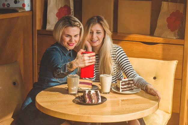 Twee gelukkige vrouwen zitten in een café en nemen selfies aan de telefoon, drinken een cocktail, vertellen elkaar grappige verhalen, zijn in een goed humeur, lachen gelukkig. beste vrienden