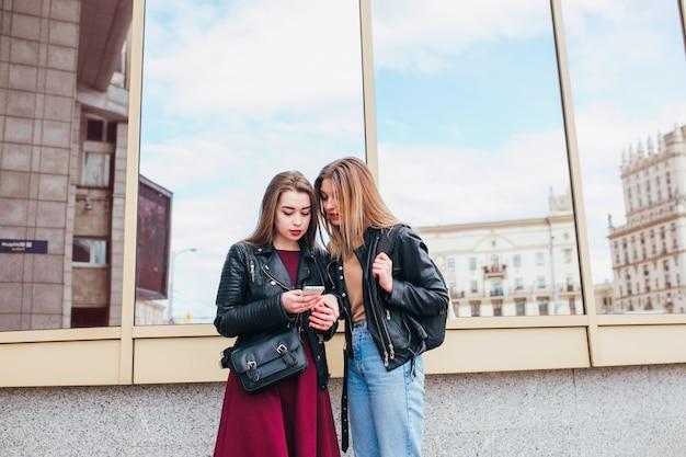 Twee gelukkige vrouwenvrienden die sociale media in een slimme telefoon in openlucht in stad delen. twee jonge vrouwen met mobiele telefoon praten