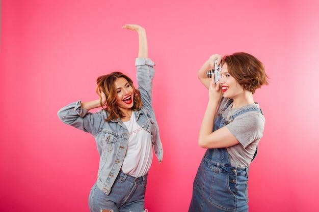 Twee gelukkige vrouwenvrienden maken foto door camera.
