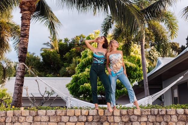 Twee gelukkige vrouwenvrienden met zonnebril op vakantie in tropisch land