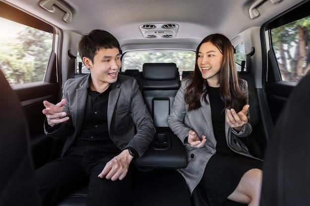 Twee gelukkige zakenman en vrouw praten terwijl ze op de achterbank van een auto zitten