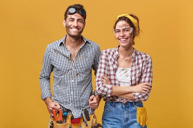 Twee gelukkige zelfverzekerde reparateurs in beschermende kleding staan naast elkaar bij blinde muur en breed glimlachend, klaar voor reparatie, reparatie en renovatie