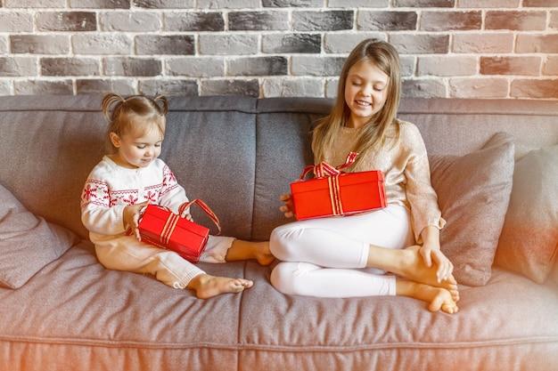 Twee gelukkige zusjes meisjes met kerstcadeaus op de bank glimlachen. kerstconcept.