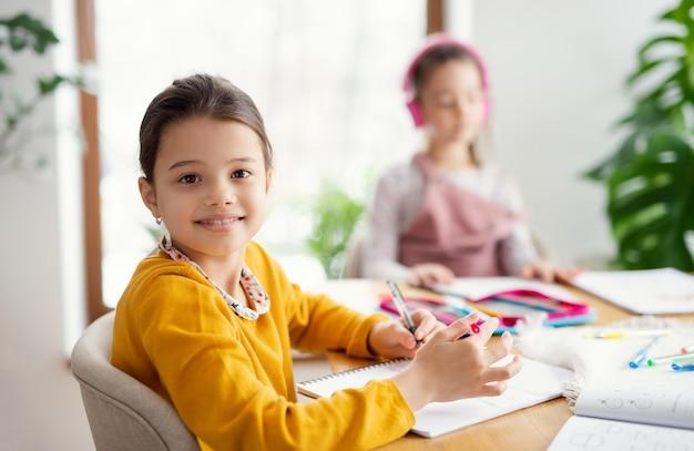 Twee gelukkige zussen van schoolmeisjes binnenshuis, afstandsonderwijs.