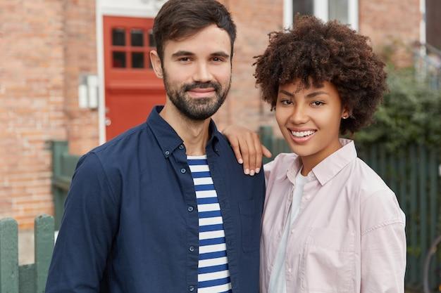 Twee gemengd ras meisje en jongen staan dicht bij elkaar, in goed humeur, buiten wandelen