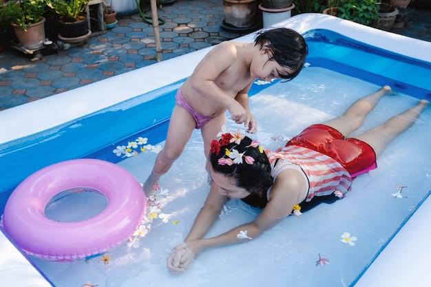 Twee generatie mensen zwemmen in zwembad in de zomer.