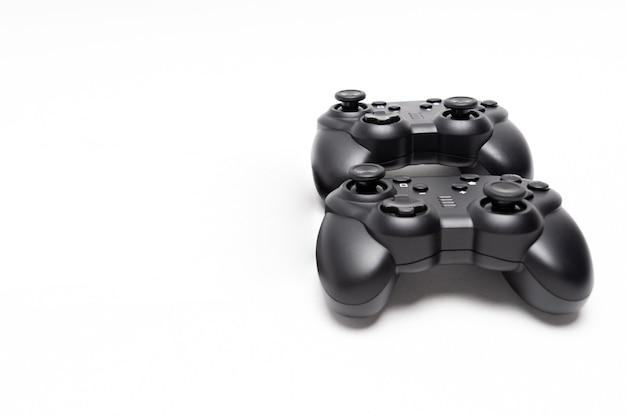Twee generieke zwarte gaming-controllers geïsoleerd op een witte achtergrond