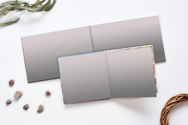 Twee geopende fotoboeken met harde kaft en blanco pagina's