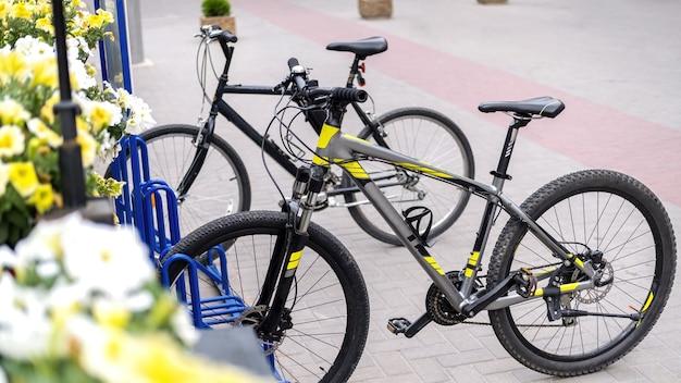 Twee geparkeerde fietsen in een straat in de buurt van een weg, bloemen