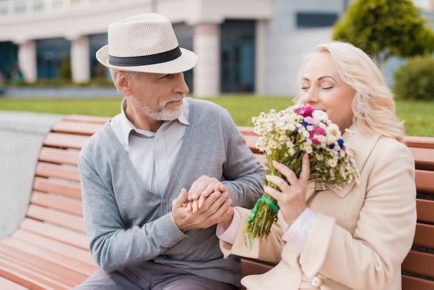Twee gepensioneerden zitten op een bankje in de steeg.