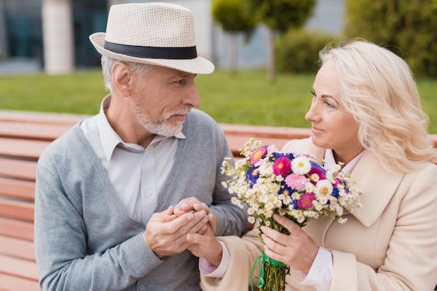 Twee gepensioneerden zitten op een bankje in het steegje