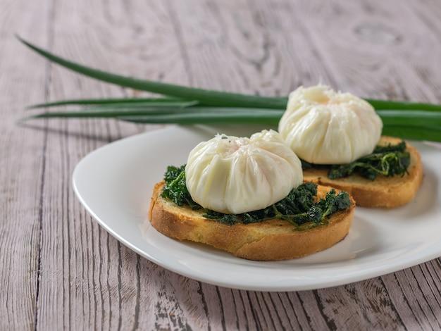Twee gepocheerde eieren met brood en groene uien op een houten tafel. vegetarische snack met gepocheerde eieren.