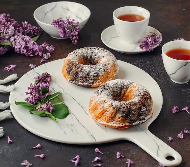 Twee geportioneerde cacao marmeren cakes op marmeren bord