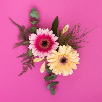 Twee gerberabloemen met takken op lijst