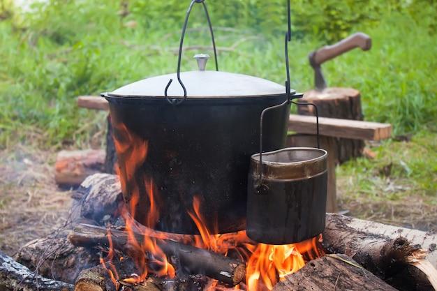 Twee gerookte toeristenketels boven kampvuur. proces van koken op de natuur