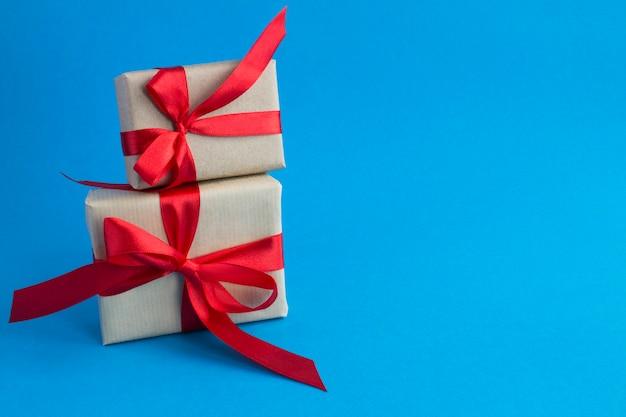 Twee geschenkdoos met gebonden rode strik op de blauwe achtergrond. ruimte kopiëren. detailopname.