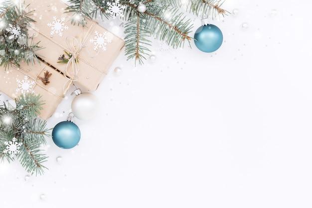 Twee geschenkdozen en kerstversiering, groene twijgen op witte achtergrond.