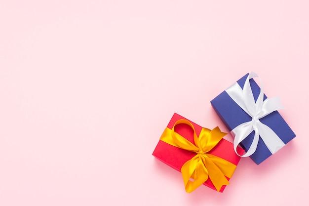 Twee geschenkdozen op een roze achtergrond. concept vakantie