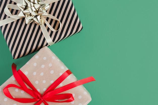 Twee geschenkdozen verpakt in kraftpapier met rode en gele linten op groene achtergrond