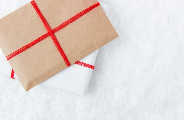 Twee geschenken in een heldere verpakking op een besneeuwde achtergrond die zich voorbereiden op de verpakkingsdozen voor de feestdagen