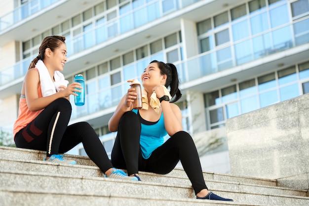 Twee geschikte aziatische meisjes die waterflessen houden en op trap in stedelijke straat zitten