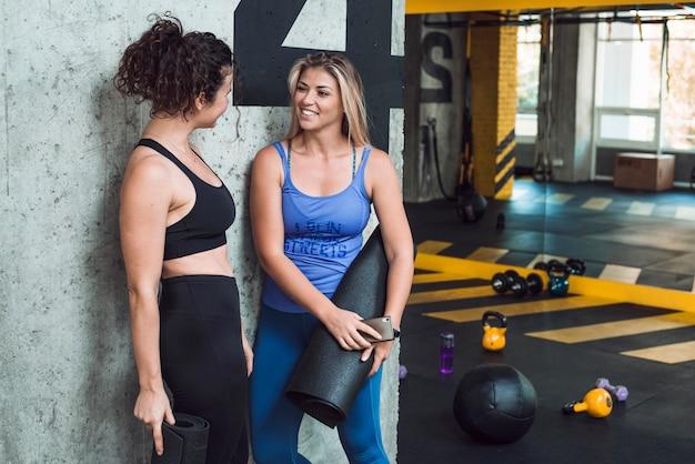 Twee geschikte jonge vrouwen met geschiktheidsmat die op muur in gymnastiek leunen