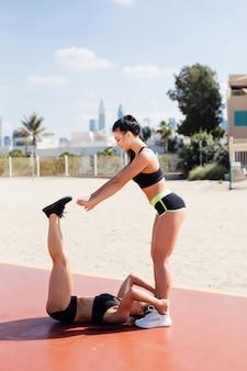 Twee geschiktheids jonge vrouwen die buikoefeningen doen bij het strand dichtbij overzees