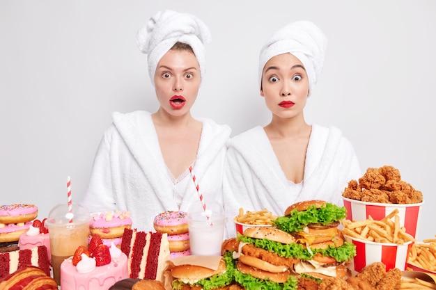 Twee geschokte dames van gemengd ras in dessingjurken geven de voorkeur aan ongezond eten verbijsterd