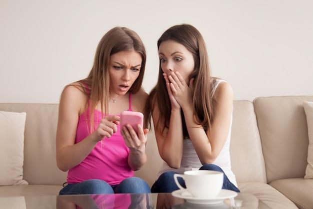 Twee geschokte jonge meisjes die het smartphonescherm bekijken.
