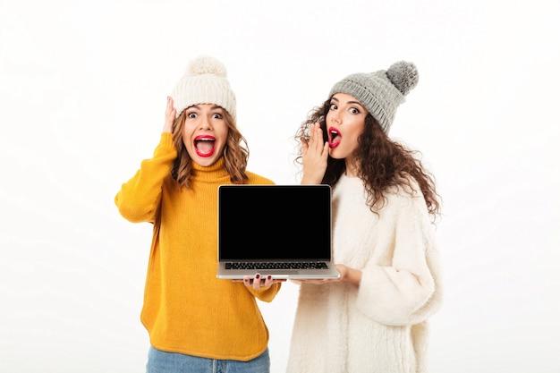 Twee geschokte meisjes in sweaters en hoeden die zich verenigen terwijl het tonen van het lege laptop computerscherm over witte muur