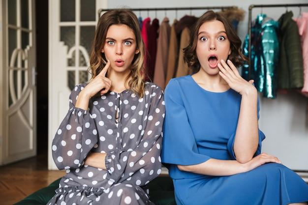 Twee geschokte vrouwen zitten binnenshuis