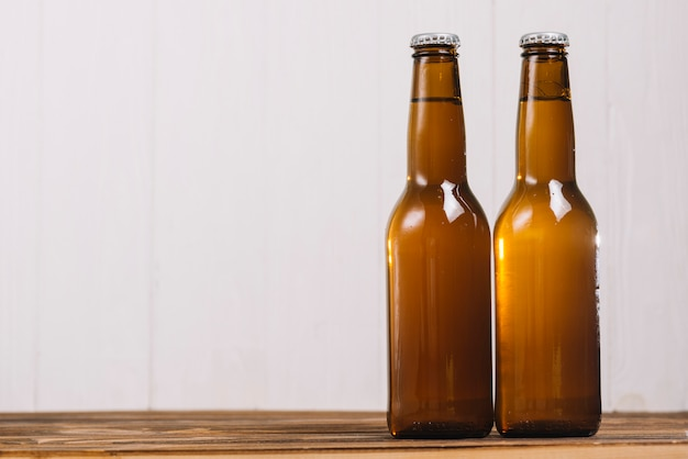 Twee gesloten bierflessen op houten bureau