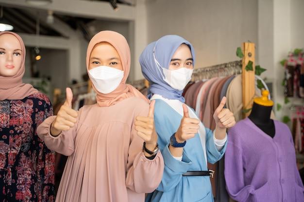 Twee gesluierde zakenvrouwen die maskers dragen met duimen omhoog terwijl ze rug aan rug staan