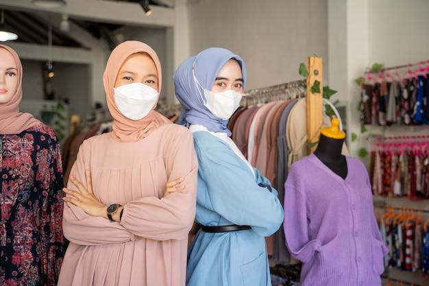 Twee gesluierde zakenvrouwen die maskers dragen met gekruiste armen terwijl ze rug aan rug staan