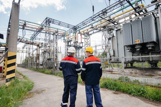 Twee gespecialiseerde ingenieurs van elektrische onderstations inspecteren moderne hoogspanningsapparatuur. energie. industrie.
