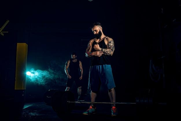 Twee gespierde, bebaarde, getatoeëerde atleten bereiden zich voor op training om de lat voor zwaargewicht hoger te leggen