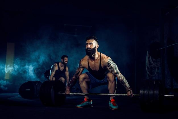 Twee gespierde, bebaarde, getatoeëerde atleten trainen, de ene tilt de zware staaf op terwijl de andere motiverend is