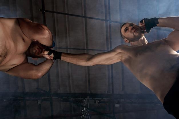 Twee gespierde mannen vechten, bodybuilders slaan elkaar, trainen in vechtsporten, boksen, jiu jitsu en mma. kickboks concept