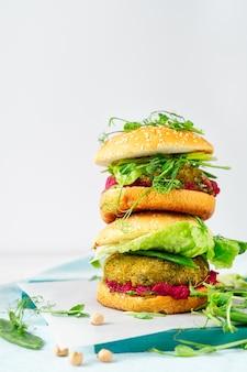 Twee gestapelde zelfgemaakte vegan hamburgers met kikkererwten pattie, groene erwten en bieten hummus