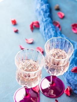 Twee gesteelde champagneglazen op blauwe texturedwith roze droge bloemen. valentijnsdag bruiloft romantische datum uitnodiging