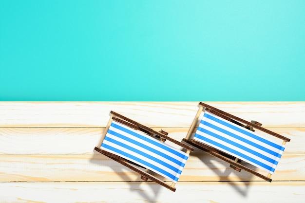Twee gestreepte strandstoelen op houten oppervlak en blauwe achtergrond